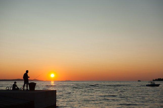 Rybar pri zapade slnka