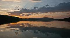 Západ letného slnka nad vodou.