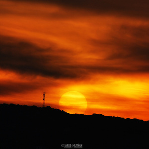 Krvavý západ slnka nad kopcami.